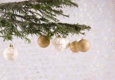 Ornaments on Christmas tree. A view of Christmas balls or ornaments hanging from a bough of a Christmas tree.  White background with shiny snowflakes Royalty Free Stock Photos