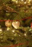 Ornaments on Christmas tree. Gold colored heart shaped ornaments and fairy lights on Christmas tree royalty free stock photos