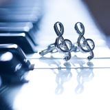 Ornaments in the form of a treble clef on piano keyboard Royalty Free Stock Photo