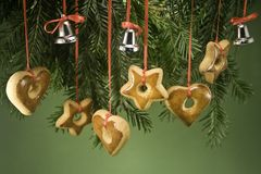 Ornaments hanging from branch. Gingerbread ornaments and tiny bells handing by ribbon under a fir branch and isolated on green paper stock images
