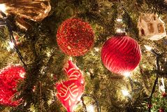 Red Christmas ornaments hanging on a tree with blurred lights in the background.. stock photos
