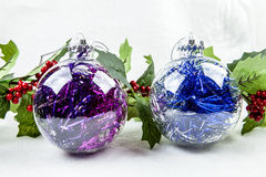 Ornaments and Holly. A pair of clear ornaments surrounded by holly Stock Photography