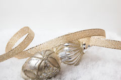 Ornaments and ribbon. Gold Christmas ornaments and ribbon on snow with a white background Royalty Free Stock Image