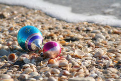 Ornaments & Shells. Two Christmas ornaments on a shell bed at the shore stock photos