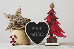 Ornaments and text merry christmas in italian. Christmas tree, some cozy ornaments in a rustic enamel pot and a heart-shaped signboard with the text buon natale stock images