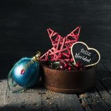 Ornaments and text merry christmas in spanish. Some cozy christmas ornaments in a wooden tray and a star-shaped black signboard with the text feliz navidad stock image