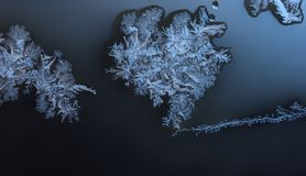 Ornaments on the window created by frost in blue. Frozen water on the window creates silver beautiful odecoration ornaments Stock Images