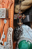 Ornate accessories. Ornate copper jewellery cross on chain against belts Royalty Free Stock Photo