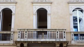 Ornate Balcony on Grand Rome Building. Ornate balcony on grand building, central Rome, Italy, with three arched doors Stock Photo