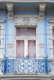 Ornate baroque window with a balcony in old blue building Royalty Free Stock Photo