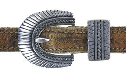 Ornate belt buckle. An ornate silver belt buckle on a very old leather belt Royalty Free Stock Images