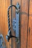 Ornate black door handle in weathered wood door Royalty Free Stock Photography