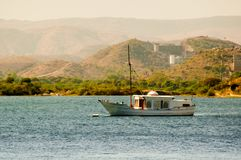 Ornate boat on a blue lake with green hills in the background. Ornate sail boat anchored on a blue lake with beautiful aravali hills in the background. Shot in Stock Images