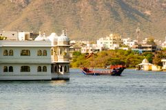 Ornate boat passing near a palace on a lake. Ornate boat passing an indian palace on a lake in Udaipur. The city itself is visible in the background as are the Royalty Free Stock Photography