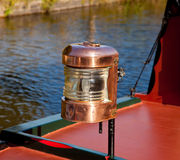 Ornate brass driving lamp on canal barge. Polished brass lamp on the bow of a canal barge stock photography