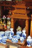 Vintage carved wooden ancestor altar with ceramics at a market in Hanoi, Vietnam. Ornate carved wooden altar for ancestor worship outfitted with blue and white stock photography