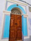 Ornate carved wooden door surrounded by blue stinework in the me. Dina in Kairouan, Tunisia. North Africa Stock Photos