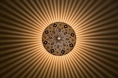 Ornate centered lamp emitting stripes stock illustration
