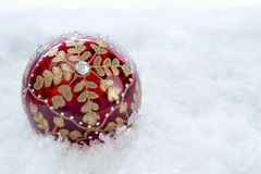 Ornate Christmas Bauble With Snow. Ornate Christmas bauble on a snow covered  backdrop with copy space Stock Photos