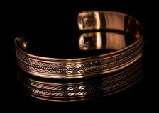 Ornate Copper Bracelet. Close up men's copper ornate bracelet isoalted on black background with reflection Stock Photos