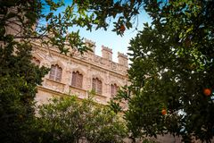 The wall through the orange trees. Ornate crenellations on the wall of the silk exchange in Valencia, Spain Royalty Free Stock Photography