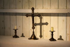 Ornate cross and candles on table Royalty Free Stock Images
