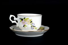 Ornate cup with saucer. Ornate porcelain cup isolated on black Royalty Free Stock Image