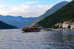 Ornate Day Cruise Boat, Bay of Kotor, Montenegro. An ornate day cruise boat crossing a narrow section of the Bay of Kotor, Montenegro, with dark Montenegrin stock photography