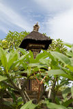 Ornate decorated spirit house with thatched roof in Bali,Indonesia. Balinese spirit house with thatched roof surrounded by frangipani trees and yellow flowers on Stock Image