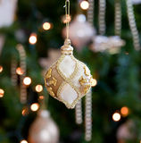 Ornate decoration in front of Christmas tree. Decorated ornament in front of an out of focus xmas tree stock images