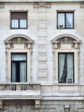 Ornate decorative windows. Decorative windows and a balcony in an Italian city of Milano Royalty Free Stock Images