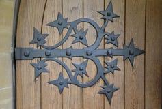 Ornate Door Hinge on Old Brown Door Stock Images