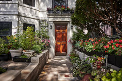 Beautiful wood door and colorful flowers. An ornate door to a townhouse with a colorful garden of flowers Royalty Free Stock Photography