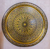 Ornate engraved brass wall plaque. Ornate engraved round brass wall plaque mounted on a white wall with a geometric repeat pattern, close up view stock image