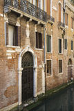 Ornate Facade of Venetian Home. Canal leading up to ornate door gate of Venetian home. Vertical shot royalty free stock image