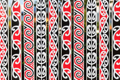 Ornate fance with Maori pattern. An ornate fence with a typical Maori pattern in red, white and black in Rotorua, New Zealand stock photo