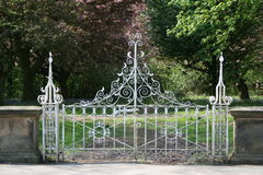 Ornate Gates. Decorative Gates in a stone wall leading to woodland stock images
