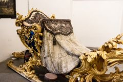 Ornate gilded sleigh with foliate decoration. Ornate historical gilded sleigh with foliate decoration on display in the Marstallmuseum in the Nymphenburg Palace Stock Image