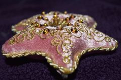 Beaautiful pink velvet pillow with gold beading. Ornate gold beading threaded throughout the beautiful pink velvet star shaped pillow Royalty Free Stock Image