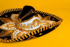 Ornate Gold, black and white Mexican sombrero. Ornate black, gold and white Mexican sombrero on a bright yellow background royalty free stock photography