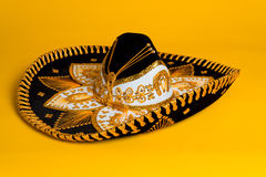 Ornate Gold, black and white Mexican sombrero. Ornate black, gold and white Mexican sombrero on a bright yellow background Stock Images