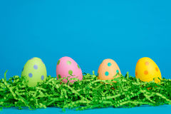 4 assorted decorated Easter eggs on a sky blue bac Stock Photos