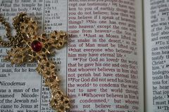 Ornate gold cross on open Bible royalty free stock photography
