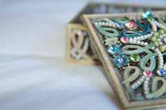 An ornate gold filigree trinket box with lid open. An ornate gold filigree trinket or jewellery box adorned with pink, blue and green gemstones and beads with Royalty Free Stock Photos