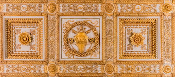 Ornate golden ceiling decorations in a basilica in Rome. Rome, Italy - October 11, 2016: Detail of an antique baroque ceiling decorations in gold covered wood Royalty Free Stock Photos
