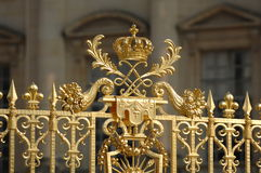 Ornate Golden Crown of Versailles. An ornate golden crown sits atop an ornate fence surrounding the Palace of Versailles in France royalty free stock images