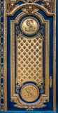 Ornate golden door with fleur de lis pattern at the entrance of Les Invalides in Paris France burial site of Napoleon Bonaparte. Ornate golden and blue door with royalty free stock images