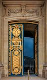 Ornate golden door with fleur de lis pattern at the entrance of Les Invalides in Paris France burial site of Napoleon Bonaparte. Ornate golden and blue door with royalty free stock photos