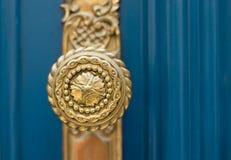 Ornate gold door handle. Ornate golden door handle closeup on blue wooden door Stock Images