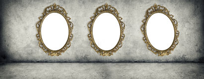 Ornate golden frames hanging on the concrete wall Stock Images